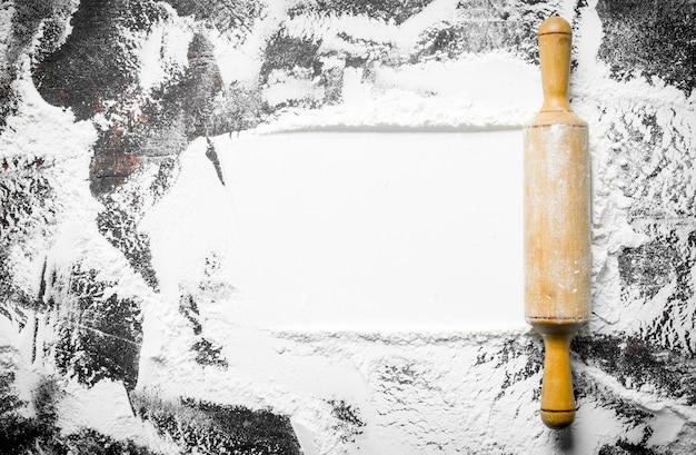 Het patroon van tarwemeel met deegroller op rustieke tafel.