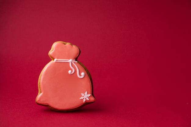 Het peperkoekkoekje sloot de rode zak van de kerstman op rood