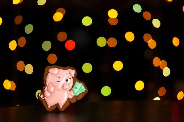 Het peperkoekkoekje van grappig roze varken van meme houdt geld defocused over gekleurde lichten van slinger.