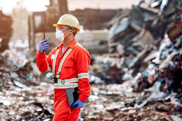 Het personeel kleedt zich strak en heeft standaardwerk. communiceren met collega's via radiocommunicatie tijdens het werken aan grootschalige afvalscheiding voor recycling