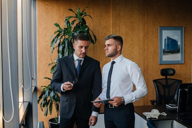 Het personeel op kantoor om zakelijke zaken naast het raam te bespreken. bedrijfsfinanciering