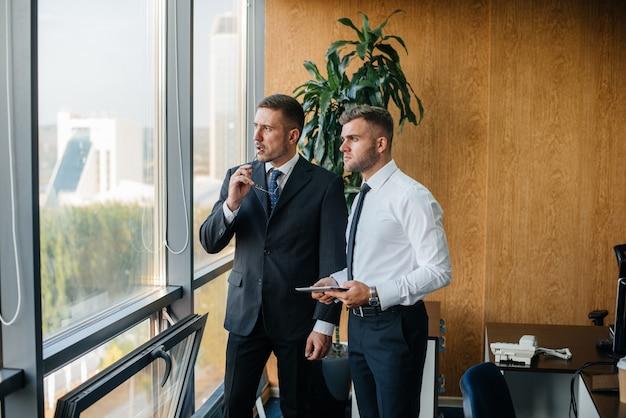 Het personeel op kantoor om zakelijke zaken naast het raam te bespreken. bedrijfsfinanciering.
