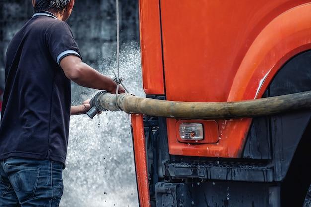 Het personeel sproeit om de weg schoon te maken.