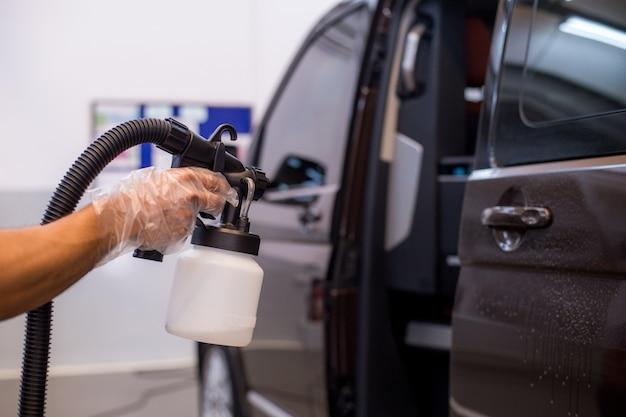 Het personeel spuit in de auto om virussen en bacteriën te voorkomen.