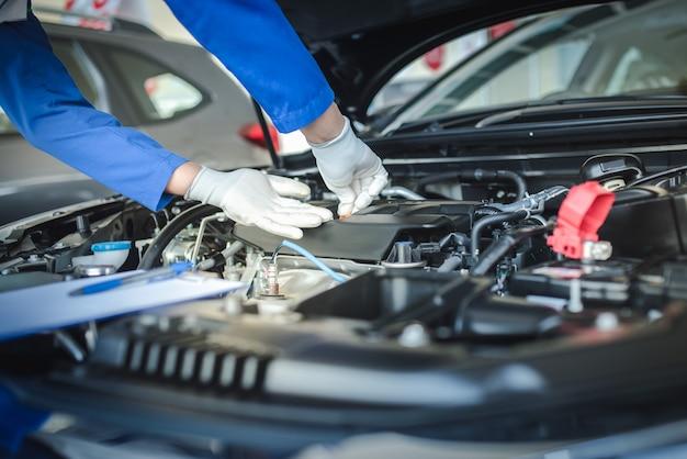 Het personeel van de automonteur trekt de oliepeilmeter omhoog om het oliepeil te controleren. om de staat van de auto te controleren