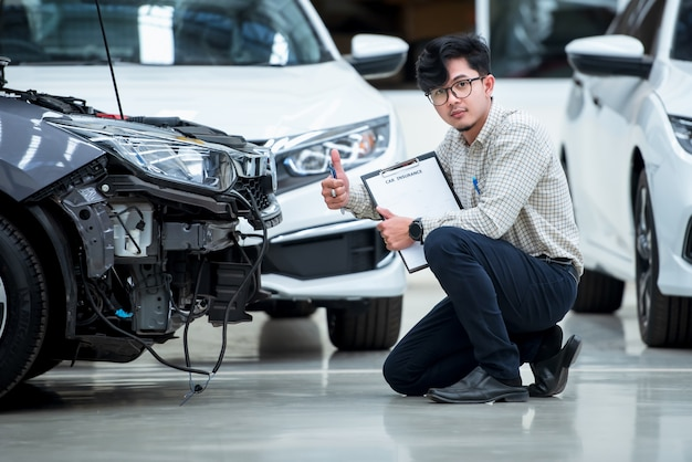 Het personeel van de verzekeringsagent schrijft op het klembord terwijl het de auto controleert na te zijn geëvalueerd en vervolgens het ongeval heeft geclaimd - de auto heeft een ongevallenverzekering.