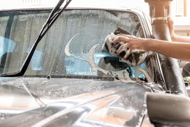 Het personeel van de wasstraat gebruikt een spons om de voorruit van de auto schoon te maken.