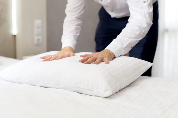 Het personeel van het hotel zet hoofdkussen op bed op