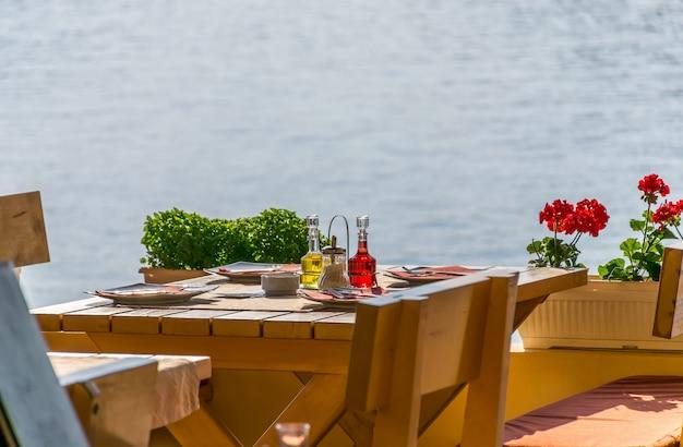 Het personeel van het restaurant bereidde hun tafels bij de zee voor het diner tijdens zonsondergang.