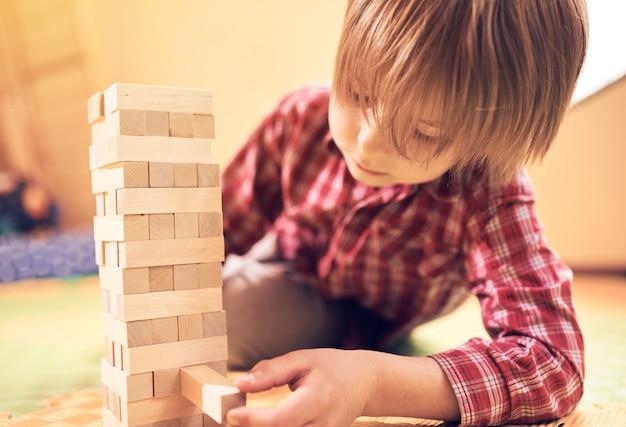 Het peuter leuke jongen spelen in een tafelspel met houten blokken thuis
