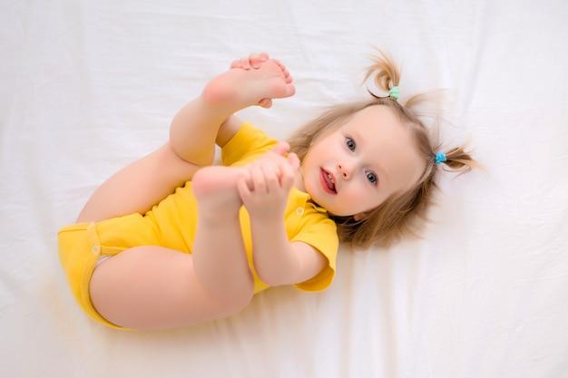 Het peutermeisje in gele bodysuit glimlacht, ligt thuis in bed