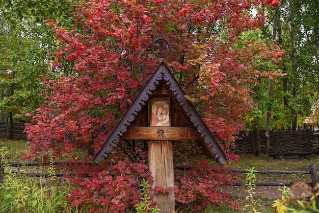Het pictogram een moeder van god maria en kind jezus christus, oud-orthodox pictogram onder een oud bladerdak naast een struik van rode viburnum