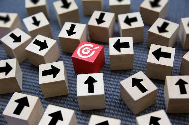 Het pijlsymbool op een houten blok dat op het doel voor bedrijfsdoelconcepten richt.