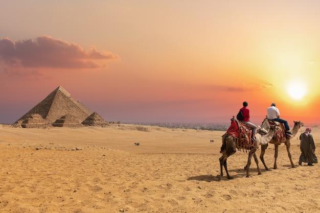 Het piramidecomplex van giza en arabieren op kamelen, egypte.