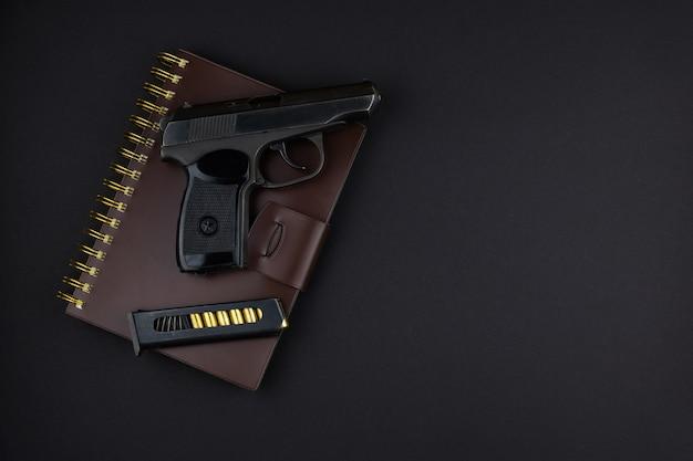 Het pistool en het geladen tijdschrift ervoor staan op een bruin in leer gebonden notitieboekje