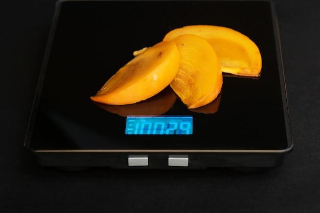 Het plakje persimmon staat op een elektronisch gewicht op een zwarte achtergrond.