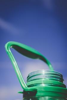 Het plastic detail van de waterfles 5l op blauwe hemel
