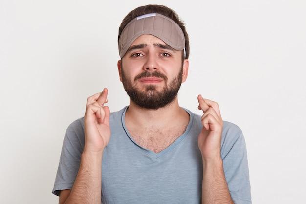 Het pleiten van streek boos geërgerde man die direct zijn vingers kruist, slaapmasker draagt, slaapproblemen heeft