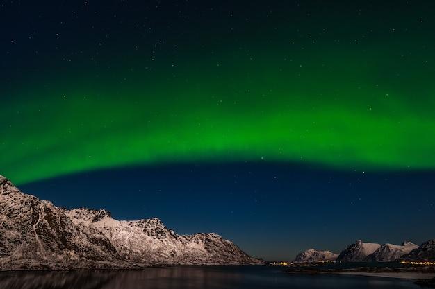 Het polaire arctische noorderlicht jaagt op aurora borealis hemelster in de bergen van de reisfotograaf van noorwegen