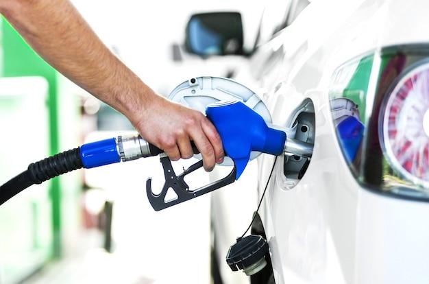 Het pompen van gas bij benzinepomp. close-up van de mens die benzine in auto bij benzinestation pompt.
