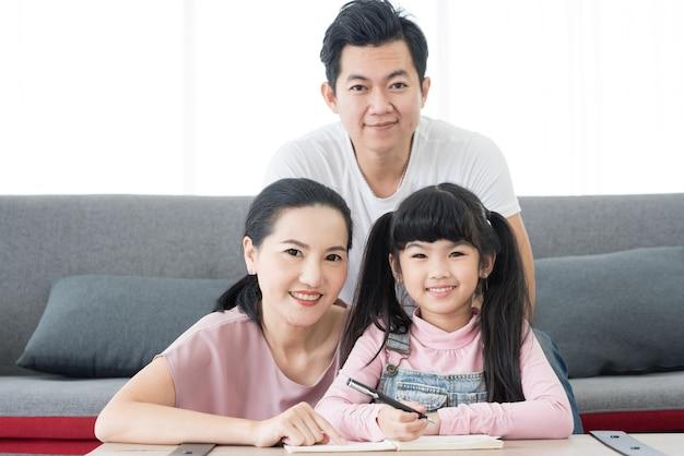 Het portret geniet van de gelukkige glimlachende vader en de moeder van de liefde aziatische familie met weinig aziatisch meisje leren
