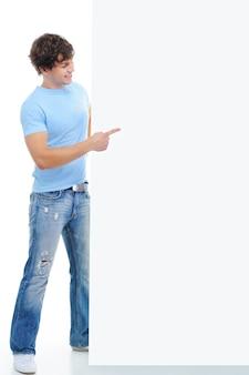 Het portret over de volledige lengte van een glimlachende jonge man duidt met de vinger op de lege banner