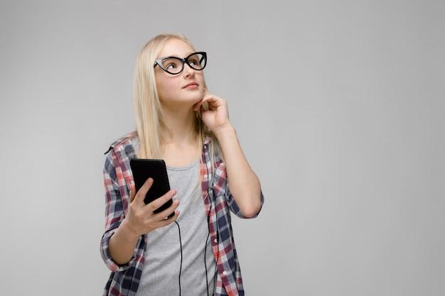 Het portret van aantrekkelijk glimlachend zoet aanbiddelijk meisje van de blondetiener in geruite kleren in glazen die mobiele telefoon in haar houden dient hoofdtelefoons op grijze achtergrond in