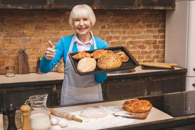 Het portret van aantrekkelijke glimlachende gelukkige hogere oude vrouw kookt op keuken. grootmoeder lekker bakken maken. duimen omhoog.