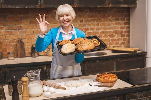 Het portret van aantrekkelijke glimlachende gelukkige hogere oude vrouw kookt op keuken. grootmoeder lekker bakken maken. ok teken.