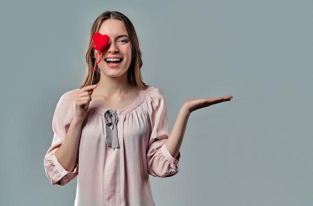 Het portret van aantrekkelijke jonge vrouw bevindt zich op grijs met rood hart in hand en houdt onzichtbaar voorwerp bij het besluit van de palmadvertentie.