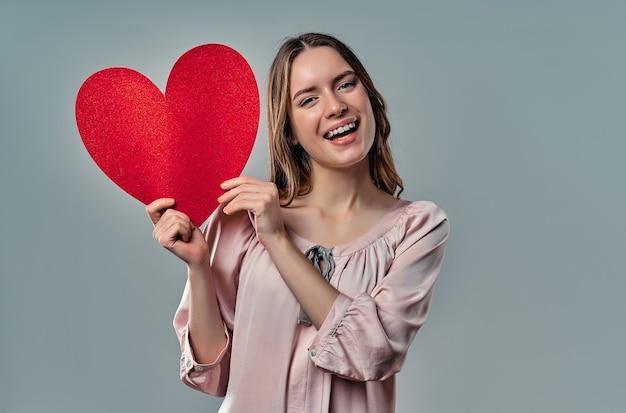 Het portret van aantrekkelijke jonge vrouw stelt op grijs met rood in hand hart.