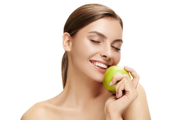 Het portret van aantrekkelijke kaukasische glimlachende vrouw die op witte muur met groene appelvruchten wordt geïsoleerd. de schoonheid, verzorging, huid, behandeling, gezondheid, spa, cosmetica