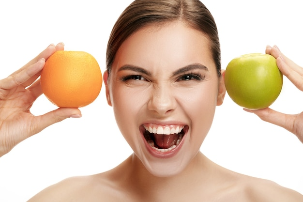 Het portret van aantrekkelijke kaukasische glimlachende vrouw die op witte studioachtergrond met groene appel en oranje vruchten wordt geïsoleerd