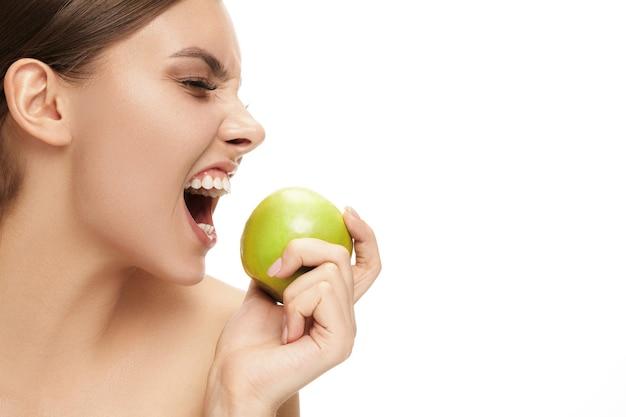 Het portret van aantrekkelijke kaukasische glimlachende vrouw die op witte studioachtergrond met groene appelvruchten wordt geïsoleerd. het concept voor schoonheid, verzorging, huid, behandeling, gezondheid, spa, cosmetica en reclame