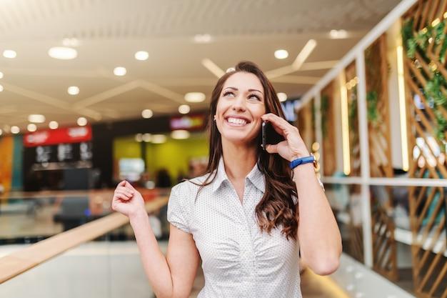 Het portret van aantrekkelijke kaukasische vrouw met lang bruin haar kleedde toevallig gebruikend slimme telefoon in winkelcomplex.