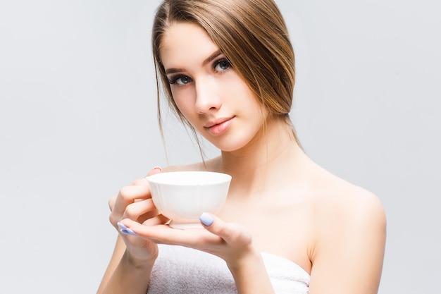 Het portret van aantrekkelijke vrouw ontspande na spa-tijd met kop thee of koffie
