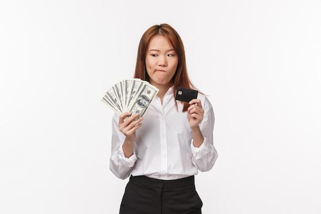 Het portret van aarzelende en twijfelachtige leuke aziatische vrouw die duur ding kopen, denkend betaalt met creditcard of contant geld, kijkend naar geld nadenkend en onzeker ben, bevindt zich witte muur