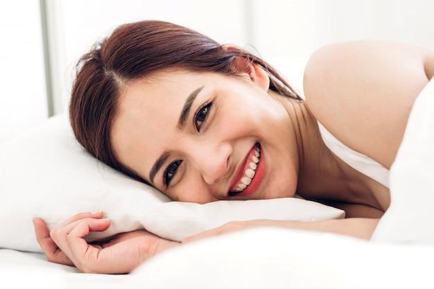 Het portret van asiannvrouw geniet van en ontspant thuis op het bed in slaapkamer. schoonheid schoonheid