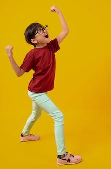 Het portret van aziatisch mooi meisje dat en hand voor succesvol, thais jong geitje met glazen in rood overhemd viert opheft is blij en vreugde op geel