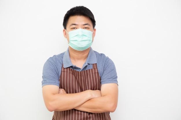 Het portret van aziatische arbeiders verse markt met bruine schort die beschermend medisch masker dragen voor verhindert virus en status met gekruiste wapens geïsoleerd op witte muur