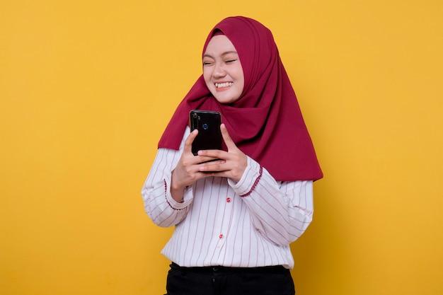 Het portret van aziatische mooie vrouw die hijab draagt, brengt een mobiele telefoon heeft pret en het glimlachen sluit haar ogengebaar