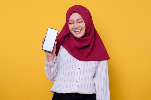 Het portret van aziatische mooie vrouw die hijab draagt, brengt een mobiele telefoon heeft pret en lacht haar ogen dicht