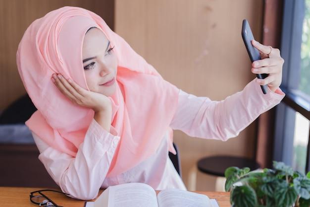 Het portret van aziatische moslim bedrijfsvrouw neemt zelf een foto. aziatische moslim bedrijfsvrouw selfie.