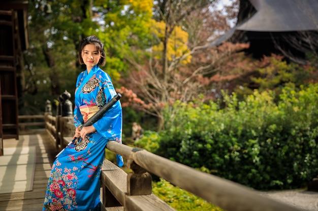 Het portret van aziatische vrouw die japanse blauwe kimono en paraplu op holding dragen dient het park in