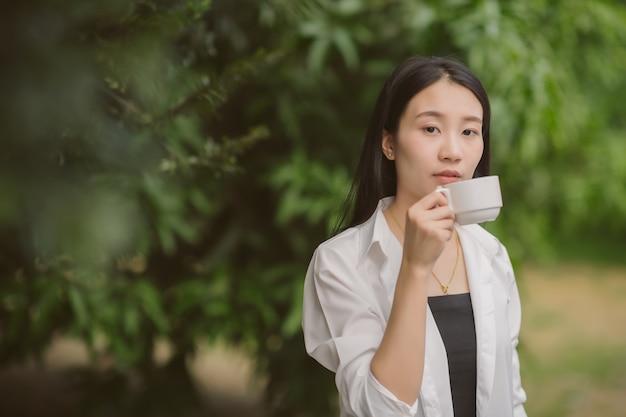 Het portret van aziatische vrouw die van meeneemkoffiekop in tuin genieten, bedrijfswijfje drinkt koffie in park.