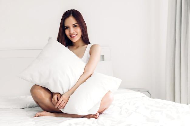 Het portret van aziatische vrouw geniet van en ontspant thuis op het bed in slaapkamer. aziatische schoonheid