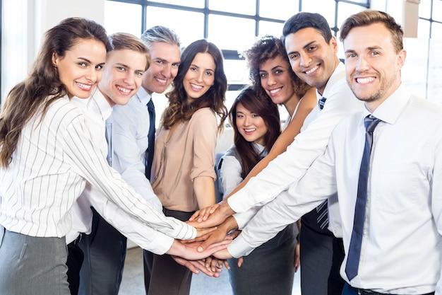 Het portret van bedrijfsmensen het stapelen dient bureau in