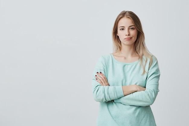 Het portret van beledigde ongelukkige mooie vrouw met lang blond haar houdt handen gekruist, buigt lippen, ontevreden met alles, voelt gefrustreerd en overstuur. negatieve emoties en gevoelens