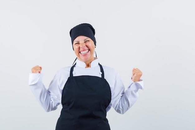 Het portret van blonde vrouw die winnaar toont stelt in zwarte uniforme kok en kijkt vrij vooraanzicht
