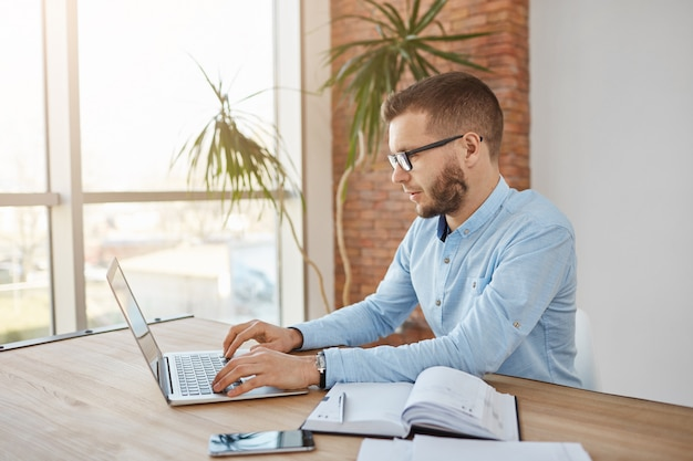 Het portret van closw omhoog van volwassen geconcentreerde ongeschoren mannelijke bedrijfaccountant in glazen en overhemdszitting in comfortabel bureau die aan laptop computer werken.